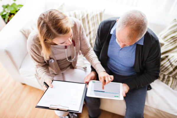 Health visitor and a senior man with tablet during home visit.
