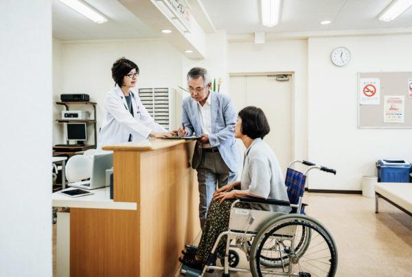 Nurse Helping Elderly Couple At Hospital Counter